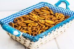 Pequeñas galletas saladas de los pretzeles en una cesta en un tabl de madera blanco Imagen de archivo