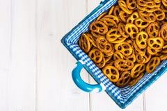 Pequeñas galletas saladas de los pretzeles en una cesta en un tabl de madera blanco Foto de archivo libre de regalías