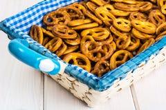 Pequeñas galletas saladas de los pretzeles en una cesta en un tabl de madera blanco Imágenes de archivo libres de regalías