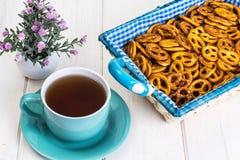 Pequeñas galletas saladas de los pretzeles en una cesta en un tabl de madera blanco Foto de archivo