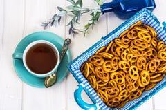 Pequeñas galletas saladas de los pretzeles en una cesta en un tabl de madera blanco Imagenes de archivo