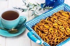 Pequeñas galletas saladas de los pretzeles en una cesta en un tabl de madera blanco Fotografía de archivo libre de regalías