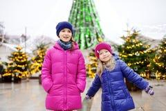 Pequeñas hermanas adorables que tienen tiempo maravilloso en mercado tradicional de la Navidad Fotografía de archivo