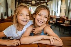 Pequeñas hermanas alegres hermosas en restaurante Foto de archivo