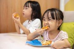 Pequeñas hermanas chinas asiáticas que comen la pizza imágenes de archivo libres de regalías
