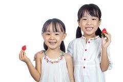 Pequeñas hermanas chinas asiáticas que sostienen la fresa Imagenes de archivo