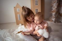 Pequeñas hermanas divertidas (hermano) que juegan en las casas de una cartulina, l Fotos de archivo