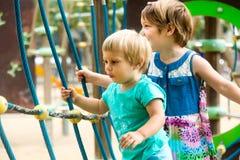 Pequeñas hermanas en el patio en parque Imágenes de archivo libres de regalías
