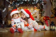 Pequeñas hermanas en pijamas en la Nochebuena fotos de archivo