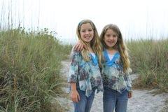 Pequeñas hermanas felices en la playa Imágenes de archivo libres de regalías