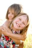 Pequeñas hermanas felices en prado verde del verano Imagenes de archivo