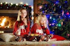 Pequeñas hermanas felices que comen leche y galletas por una chimenea en una sala de estar oscura acogedora el Nochebuena Imágenes de archivo libres de regalías