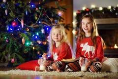 Pequeñas hermanas felices que comen leche y galletas por una chimenea en una sala de estar oscura acogedora el Nochebuena Imagen de archivo libre de regalías