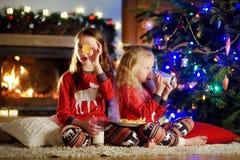 Pequeñas hermanas felices que comen leche y galletas por una chimenea en una sala de estar oscura acogedora el Nochebuena Foto de archivo libre de regalías