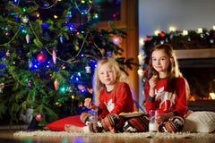 Pequeñas hermanas felices que comen leche y galletas por una chimenea en una sala de estar oscura acogedora el Nochebuena Fotos de archivo libres de regalías