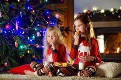 Pequeñas hermanas felices que comen leche y galletas por una chimenea en una sala de estar oscura acogedora el Nochebuena Fotografía de archivo libre de regalías