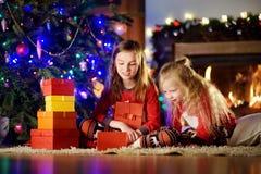 Pequeñas hermanas felices que llevan los pijamas de la Navidad que juegan por una chimenea en una sala de estar oscura acogedora  Foto de archivo libre de regalías