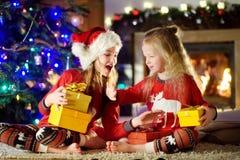 Pequeñas hermanas felices que llevan los pijamas de la Navidad que juegan por una chimenea en una sala de estar oscura acogedora  Fotos de archivo libres de regalías