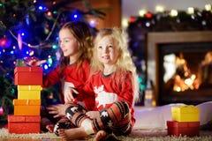 Pequeñas hermanas felices que llevan los pijamas de la Navidad que juegan por una chimenea en una sala de estar oscura acogedora  Imagen de archivo libre de regalías