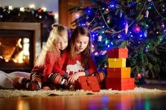 Pequeñas hermanas felices que llevan los pijamas de la Navidad que juegan por una chimenea en una sala de estar oscura acogedora  Fotos de archivo