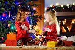 Pequeñas hermanas felices que llevan los pijamas de la Navidad que juegan por una chimenea en una sala de estar oscura acogedora  Fotografía de archivo