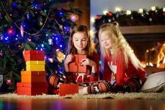 Pequeñas hermanas felices que llevan los pijamas de la Navidad que juegan por una chimenea en una sala de estar oscura acogedora  Fotografía de archivo libre de regalías