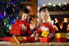 Pequeñas hermanas felices que llevan los pijamas de la Navidad que juegan por una chimenea en una sala de estar oscura acogedora  Foto de archivo