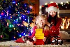 Pequeñas hermanas felices que llevan los sombreros de Papá Noel que juegan por una chimenea en una sala de estar oscura acogedora Fotografía de archivo