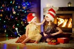 Pequeñas hermanas felices que llevan los sombreros de Papá Noel que juegan por una chimenea en la Navidad Foto de archivo libre de regalías