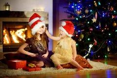 Pequeñas hermanas felices que llevan los sombreros de Papá Noel que juegan por una chimenea en la Navidad Fotografía de archivo