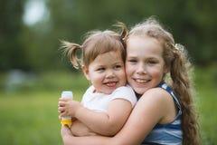 Pequeñas hermanas felices - retrato en parque Imágenes de archivo libres de regalías