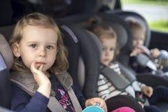 Pequeñas hermanas lindas en asientos de carro en el coche Fotografía de archivo libre de regalías