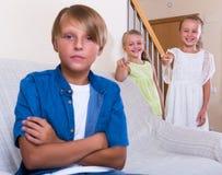 Pequeñas hermanas que toman el pelo al hermano mayor Fotografía de archivo