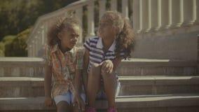 Pequeñas hermanas sonrientes que enlazan y que abrazan al aire libre almacen de metraje de vídeo