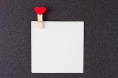 Pequeñas hojas de papel en pinza con los corazones rojos Fotografía de archivo