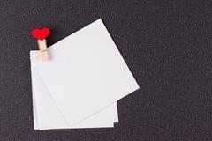 Pequeñas hojas de papel en pinza con los corazones rojos Foto de archivo libre de regalías
