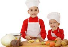 Pequeñas jefe-cocinas sonrientes en el escritorio Fotos de archivo