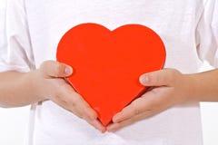 Pequeñas manos con el corazón de las tarjetas del día de San Valentín Imagen de archivo libre de regalías