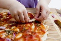 Pequeñas manos que preparan la pizza imagen de archivo libre de regalías