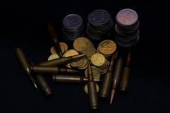 Pequeñas monedas ucranianas con la munición militar del rifle en fondo negro Simboliza la guerra para el dinero fotos de archivo
