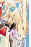 Pequeñas muchacha y pared de la pintada Imagen de archivo libre de regalías
