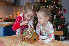 Pequeñas muchachas adorables que adornan la casa de pan de jengibre fotografía de archivo libre de regalías
