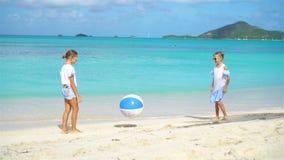 Pequeñas muchachas adorables que juegan con la bola en la playa almacen de metraje de vídeo