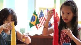 Pequeñas muchachas asiáticas que apilan bloques del montessori metrajes