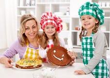 Pequeñas muchachas del cocinero con su madre que hace una torta Imagen de archivo libre de regalías
