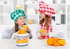Pequeñas muchachas del cocinero que prueban el zumo de naranja que hicieron Imagen de archivo libre de regalías