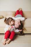 Pequeñas muchachas lindas en el sofá al revés Fotos de archivo libres de regalías