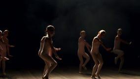 Pequeñas muchachas lindas que bailan ballet en etapa del teatro en fondo negro en humo metrajes