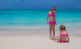 Pequeñas muchachas lindas que caminan en la playa blanca durante Imagen de archivo libre de regalías