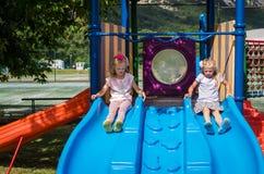 Pequeñas muchachas preciosas que juegan con la diapositiva en patio imágenes de archivo libres de regalías